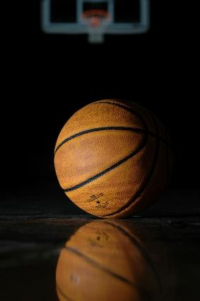Image of a basketball on a darkened court