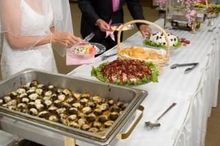 Bride and groom filling plates at the wedding buffet