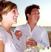 Bride and groom in white, comfortable beach attire