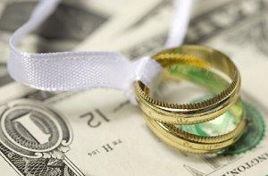 Image of gold wedding bands on money
