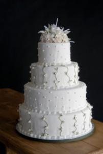 4-tier wedding cake topped with white roses