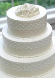 White wedding cake with seashell cake topper