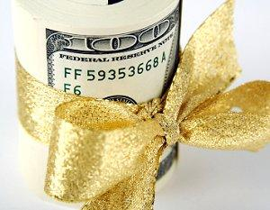 Roll of $100 bills tied with gold ribbon