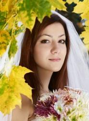 Bride standing amongst autumn leaves