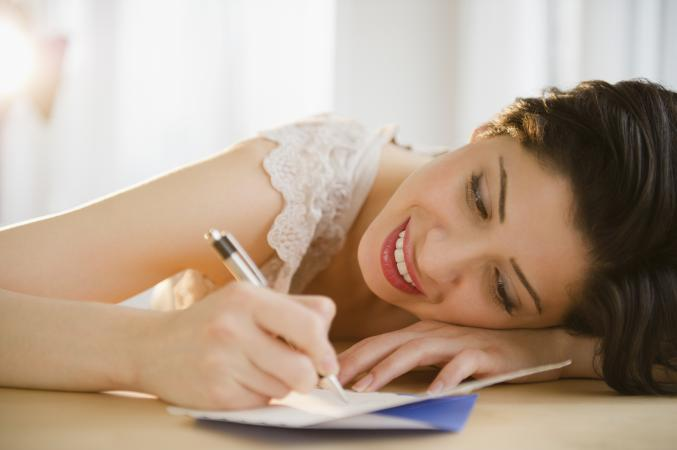 Woman writing on Thank You card