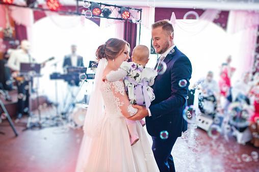 wedding couple holding baby