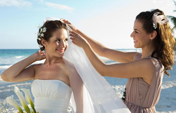 Bridesmaid adjusting bride's veil