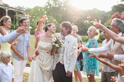 Guests throwing rose petals on bridal couple