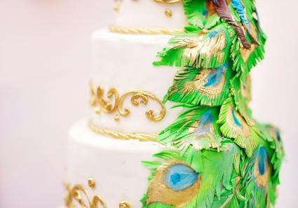 white wedding cake with peacock feathers