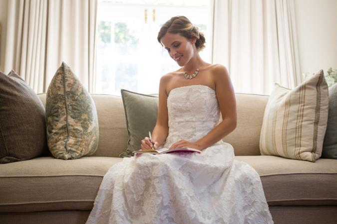 Beautiful bride writing in planner