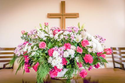 Christian cross and flowers on altar