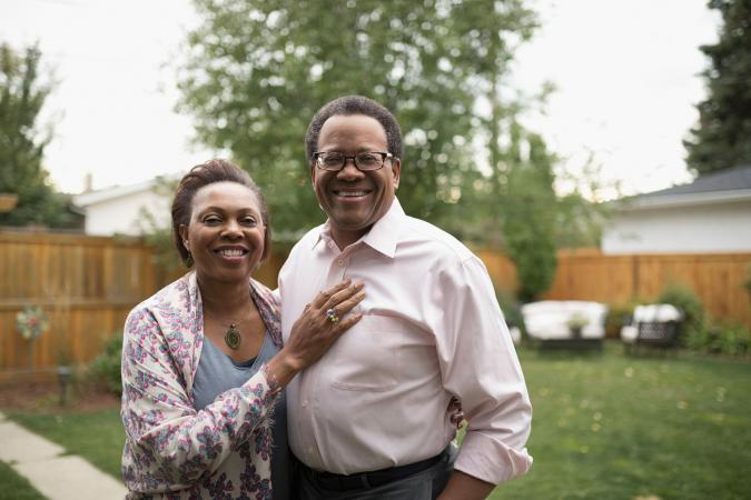 smiling senior couple hugging in backyard