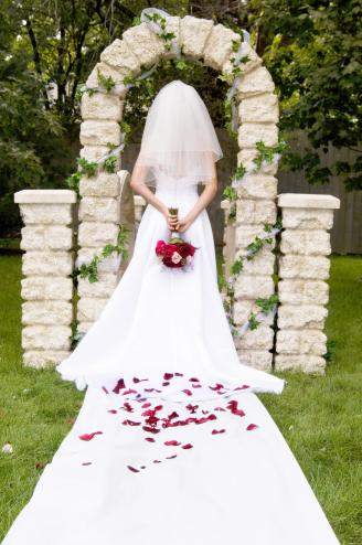 Bride wearing white wedding dress under arch
