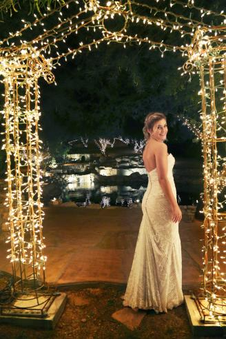 Bride standing under arch with lights