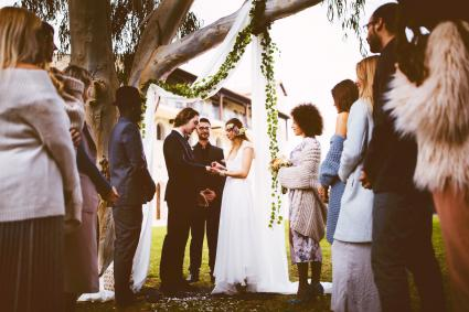 Young bride and groom getting married and exchanging rings outdoors