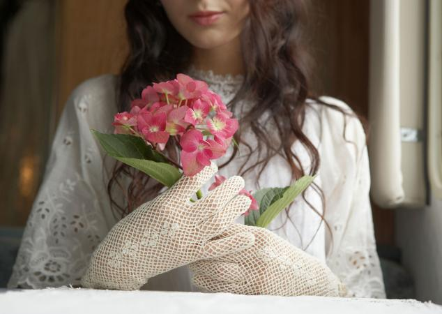 Bride holding pink hydrangeas at window