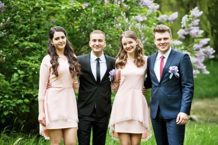 Bridesmaids in pink dresses posing with handsome groomsmen