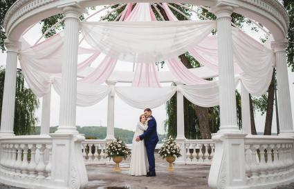 Wedding couple under large arch