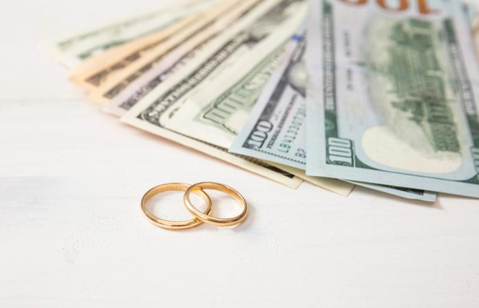 Golden wedding rings and banknotes dollars