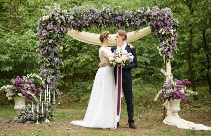 Bride and groom near the arch of lilac