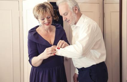 Woman buttoning senior man's shirt