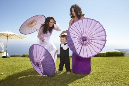 Two ladies carry purple paper parasols