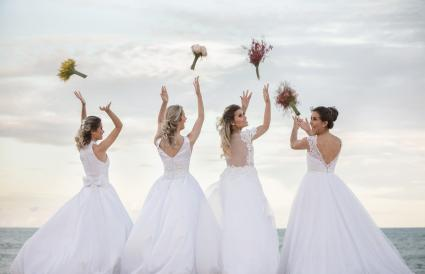 Brides Throwing Bouquets Against Sky