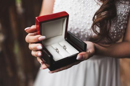 Bride holding pearl earrings in box