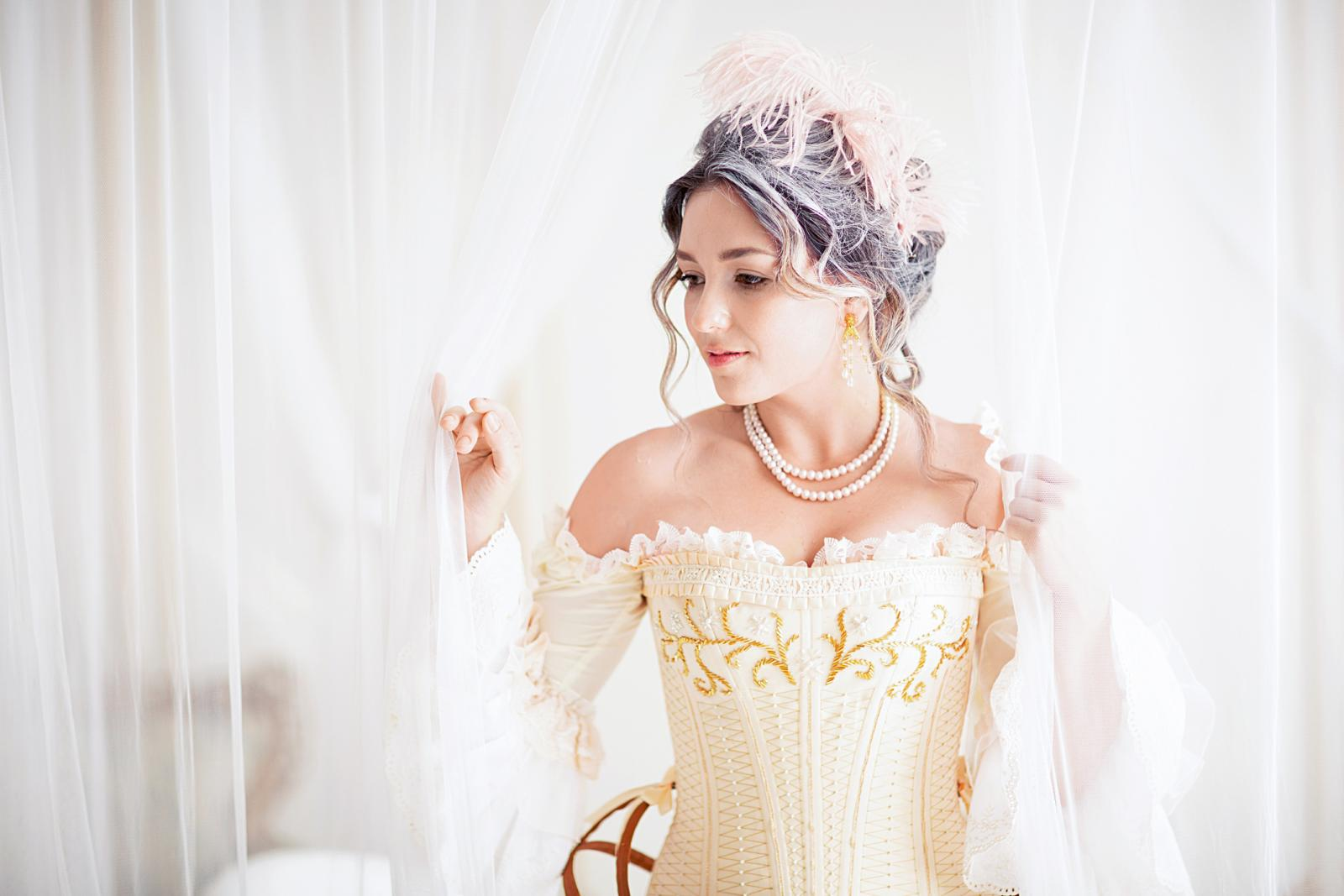 A greyhead woman with a beautiful luxurious rococo hair style in a white dress