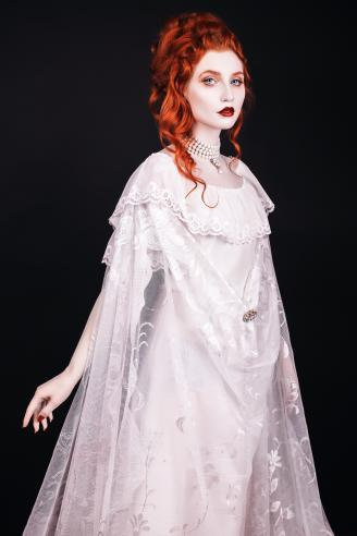 Red-haired woman in white dress with pale skin