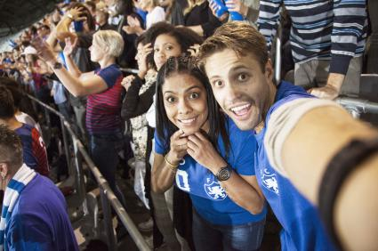 Young couple at football match taking a selfie