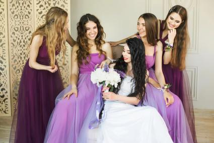 Bride holding a wedding bouquet and smiling while talking to her bridesmaids in purple dresses