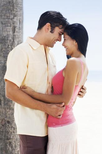 Young woman and a mid adult man embracing each other and smiling