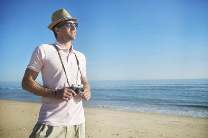 Man wearing a polo and holding a camera at the beach