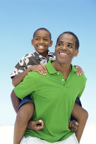 Son riding piggyback on his father