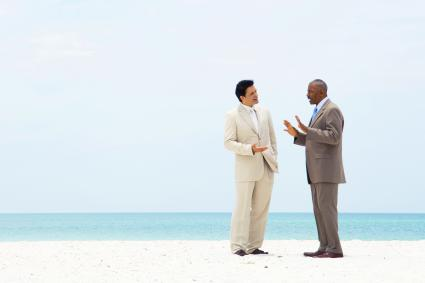 Two businessman standing on beach having conversation