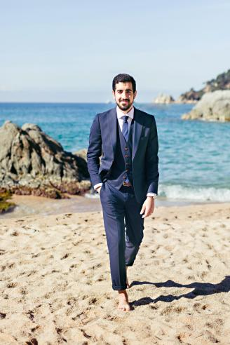 Smiling Bridegroom Walking At Beach Against Clear Sky During Sunny Day