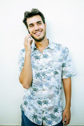 Man with cell phone with a tropical shirt