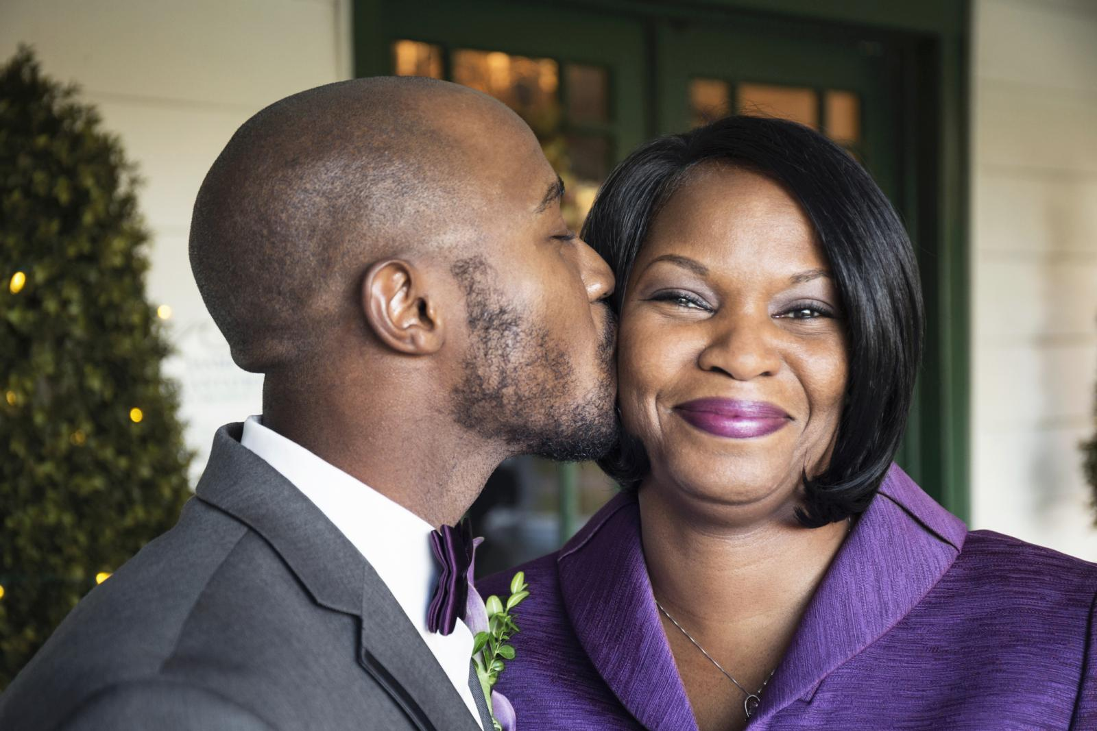 Groom kissing mother at wedding