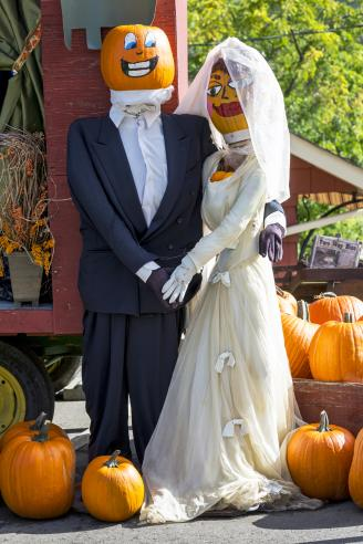 Dressed up mannequins as a married couple with painted pumpkin heads surrounded by pumpkins