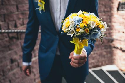 groom in an elegant blue suit is holding a beautiful bouquet of blue, yellow and ivory flowers
