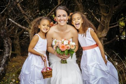 Flower girls smiling with bride outdoors