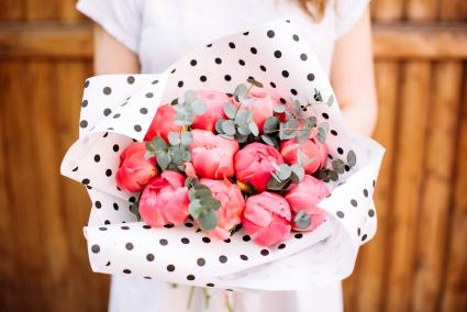 Woman holding peonies in black and white polka dot tissue