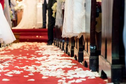 Flower petals on red carpet floor in church