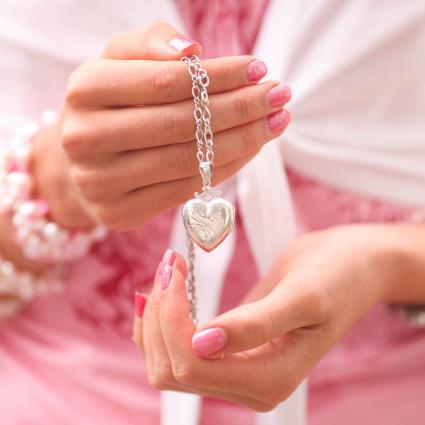 Female Hands Holding Heart Locket