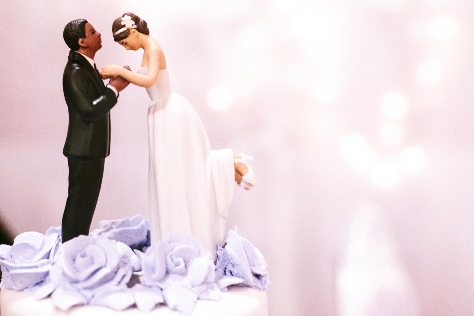 Bride and bridegroom cake decoration on top of wedding cake