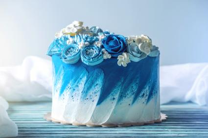 Beautiful blue wedding cake decorated with white flowers of cream