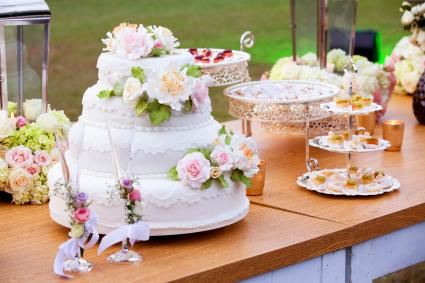 Delicious cake, flowers and catering on a wedding table