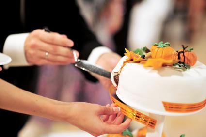 The bride and groom cut a beautiful wedding white cake decorated with orange pumpkins