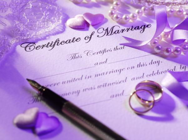 Certificate of marriage with rings, pen, hearts and a pearl necklace